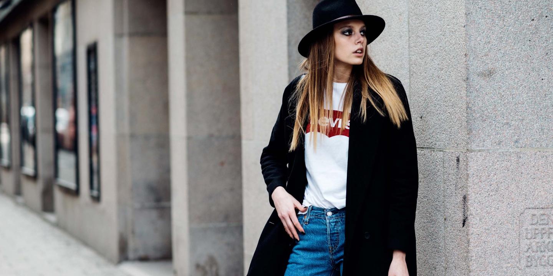 Foto de uma modelo loira, branca, com chápeu e sobre tudo pretos, com uma camisa branca da Levi's fazendo pose em uma calçada
